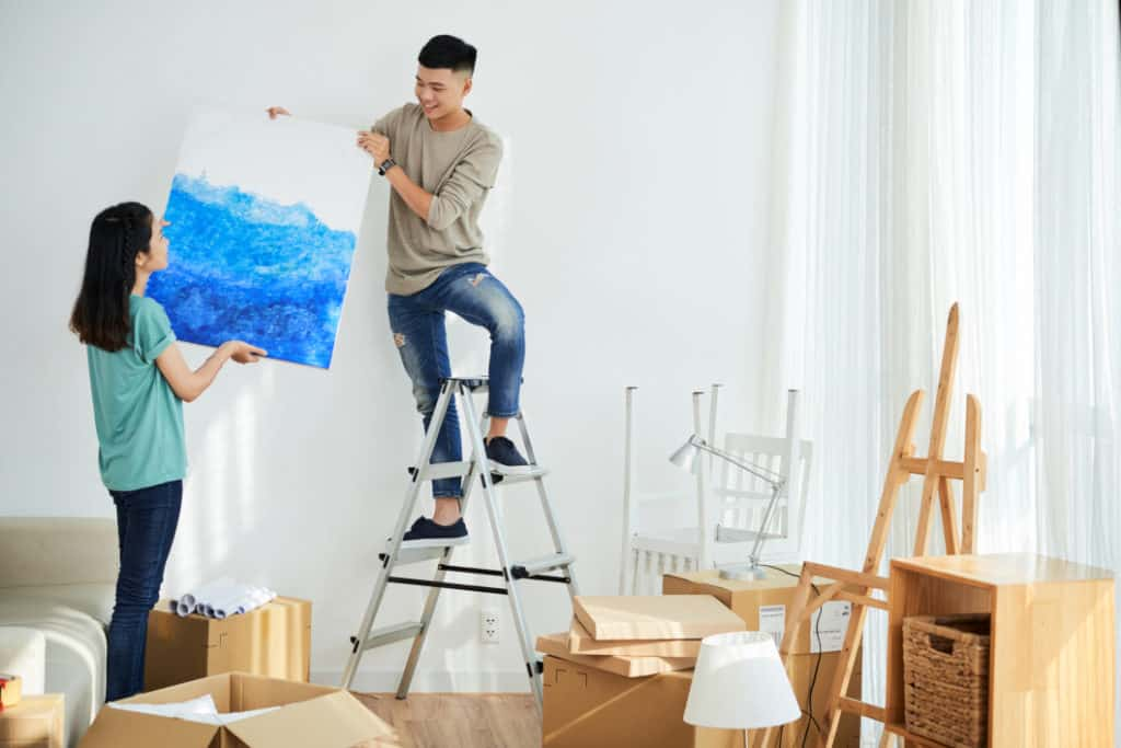 Couple hanging canvas art talking questioning can humidity damage paintings
