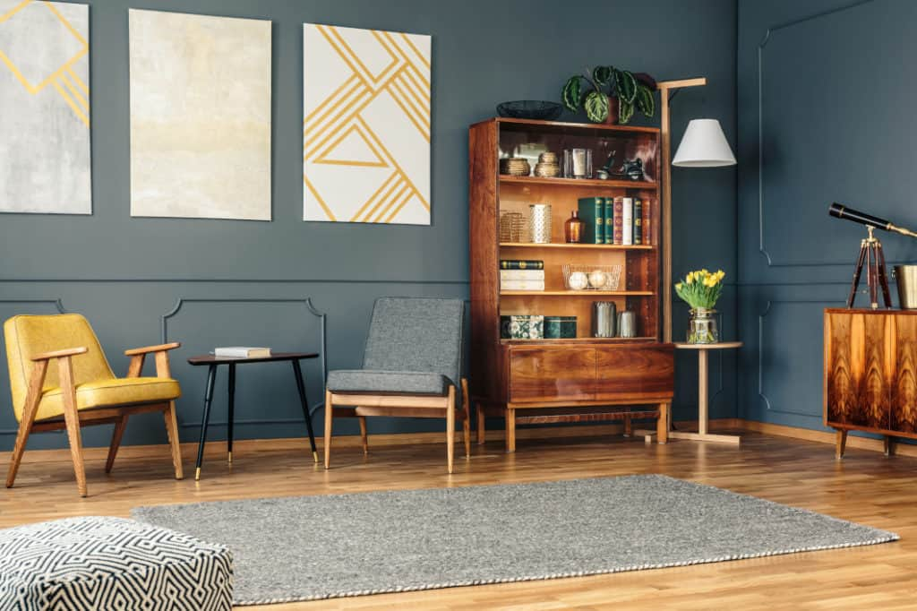 Designer living room with furniture and grouping of 3 similar paintings at home