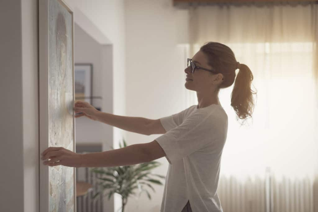 Woman deciding how to display paintings at home