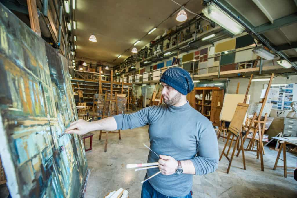 Painter creating a painting during an open studio event where collectors can find local artists