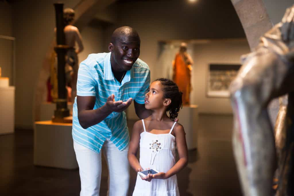 Man showing his daughter a sculpture to teach how to appreciate art without becoming a snob.