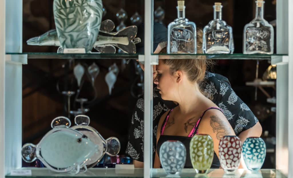 Woman who is snobby about art walking away from glass art display.