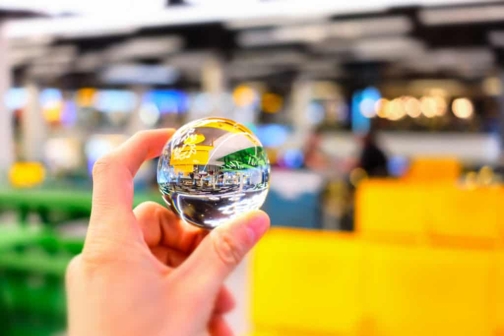 Hand holding glass ball flips the image to show how changing your perspective can help you appreciate art.