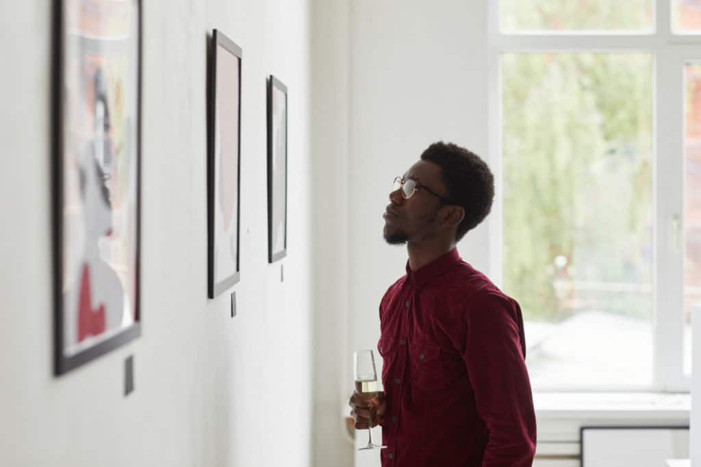 Man staring at illustrations in a gallery after learning what is art appreciation