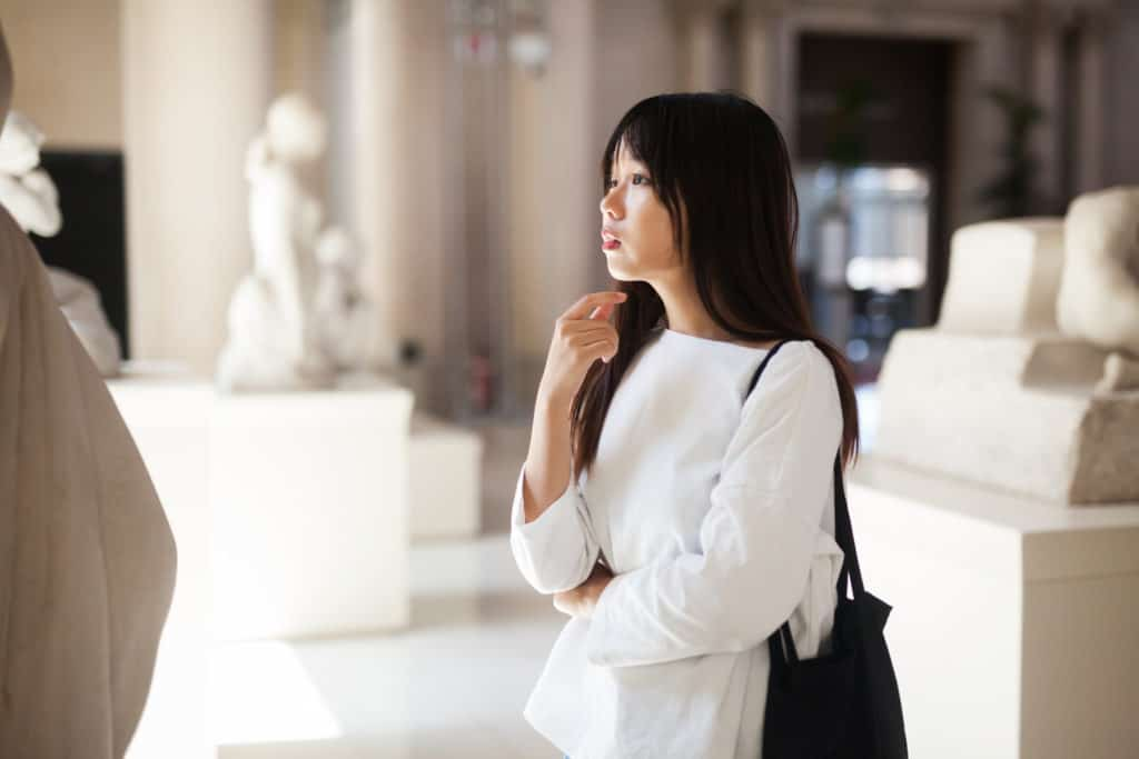 Woman looking at sculpture in a museum to learn what is art appreciation