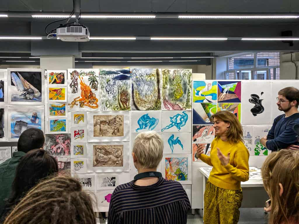 People viewing art at an arts degree show for emerging artists.