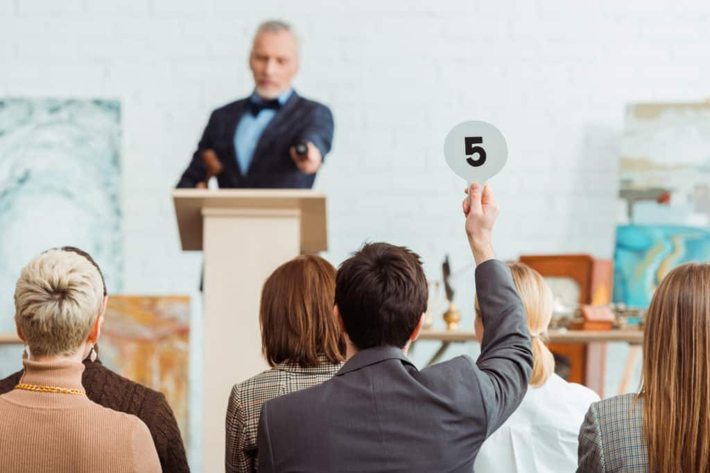 Man bidding at an art auction after identifying his art style.