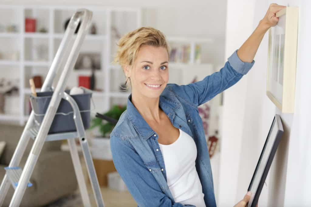 Woman hanging art in her living room after having identified her art style.