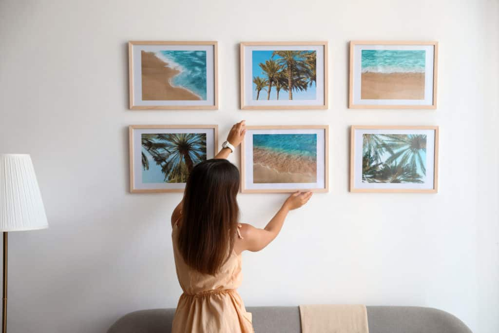 Woman hanging beach prints as she identifies her art style.