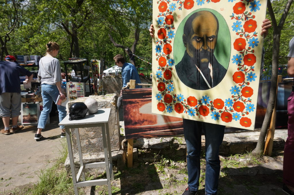 People searching through budget art pieces at a garage sale.