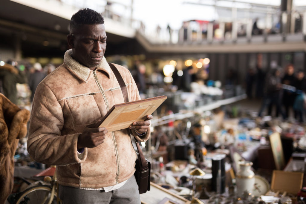 Man at a flea market where he's can buy art on a budget