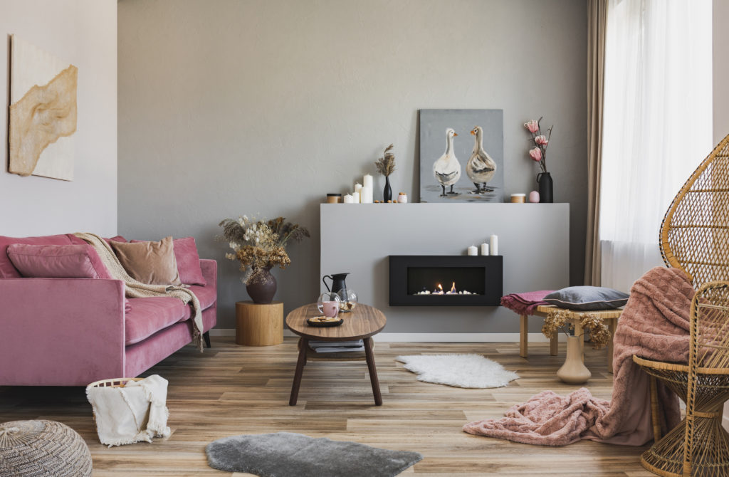 Stylish living room with painting leaned against wall atop fireplace mantle