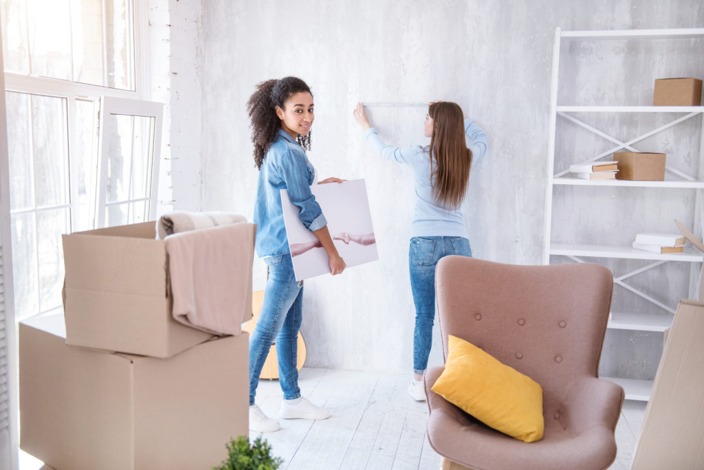 One woman holds a canvas print while another attaches adhesive tape to wall