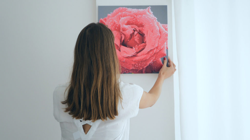 Woman holding picture wondering how to hang wall art without nails