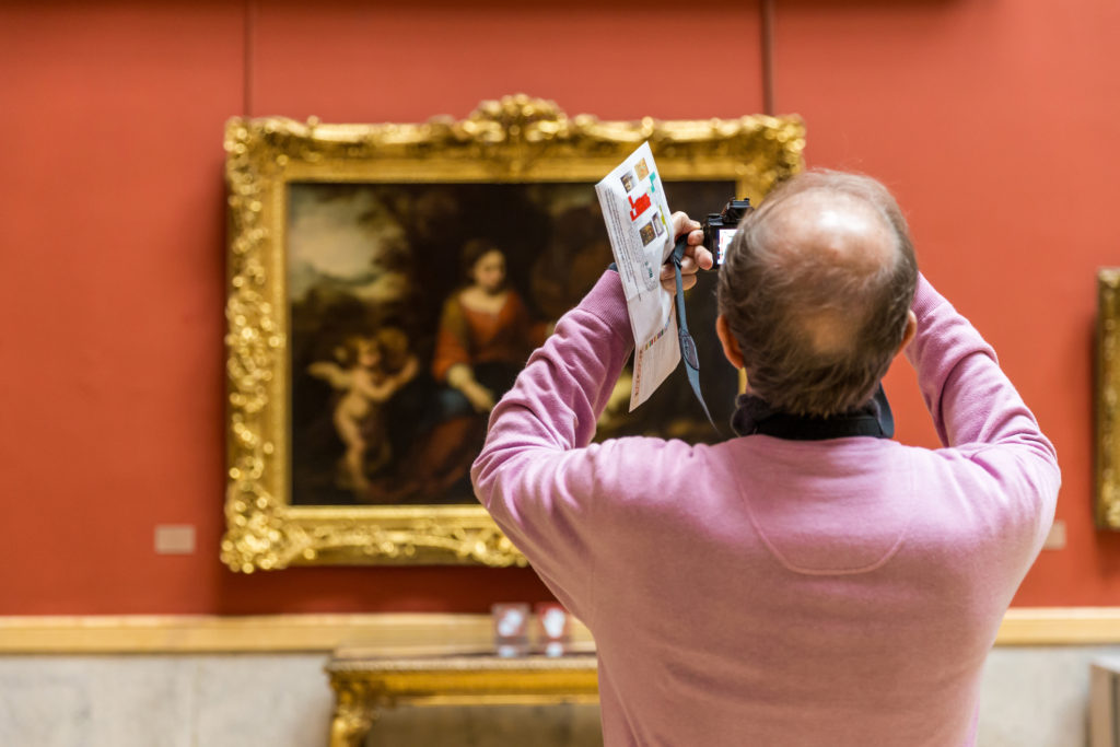 Tourist with DSLR taking a photo having learned how to photograph paintings in a museum