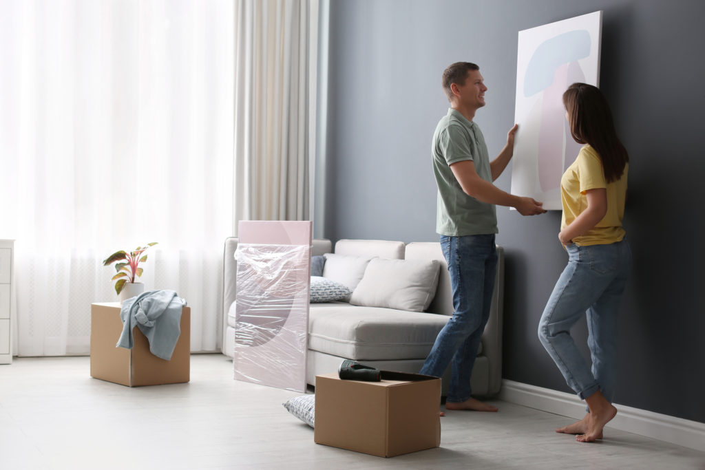 Couple removing wall painting having learned how to store artwork
