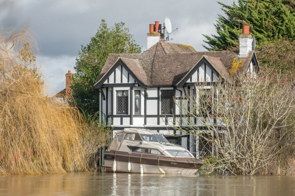 Flooding caused a boat to rise to the second level of tudor-style house.