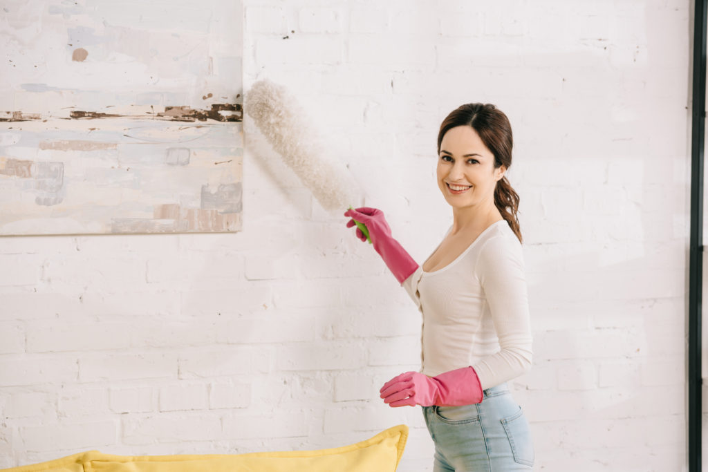 Woman about to dust though it's not the best way to clean a painting