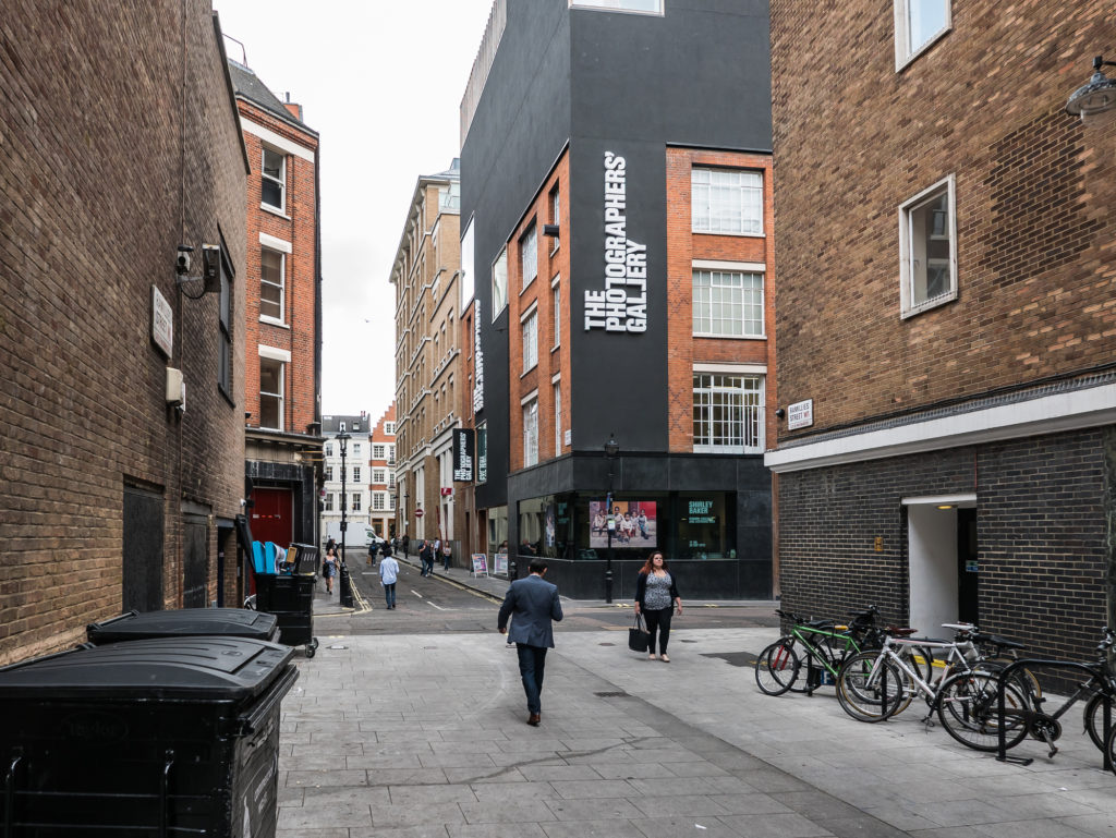 People walking down the street in front of The Photographer's Gallery in London