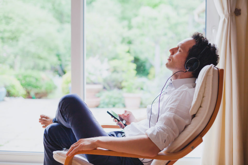 Man sitting in armchair listening to podcast to encourage creativity.