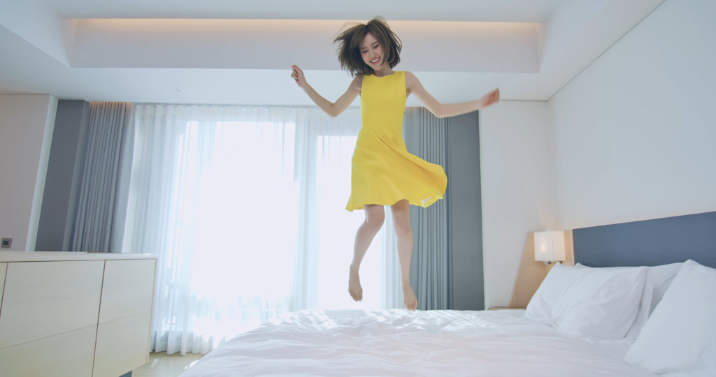Woman jumping on bed in a yellow dress.