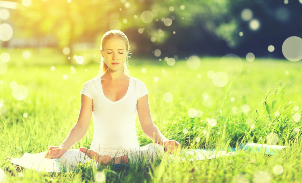 Woman meditating in a grassy meadow.