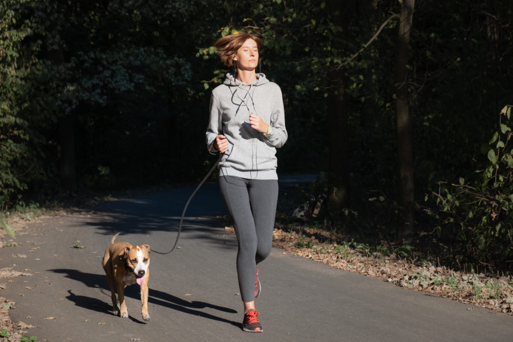 Woman jogging with her dog.