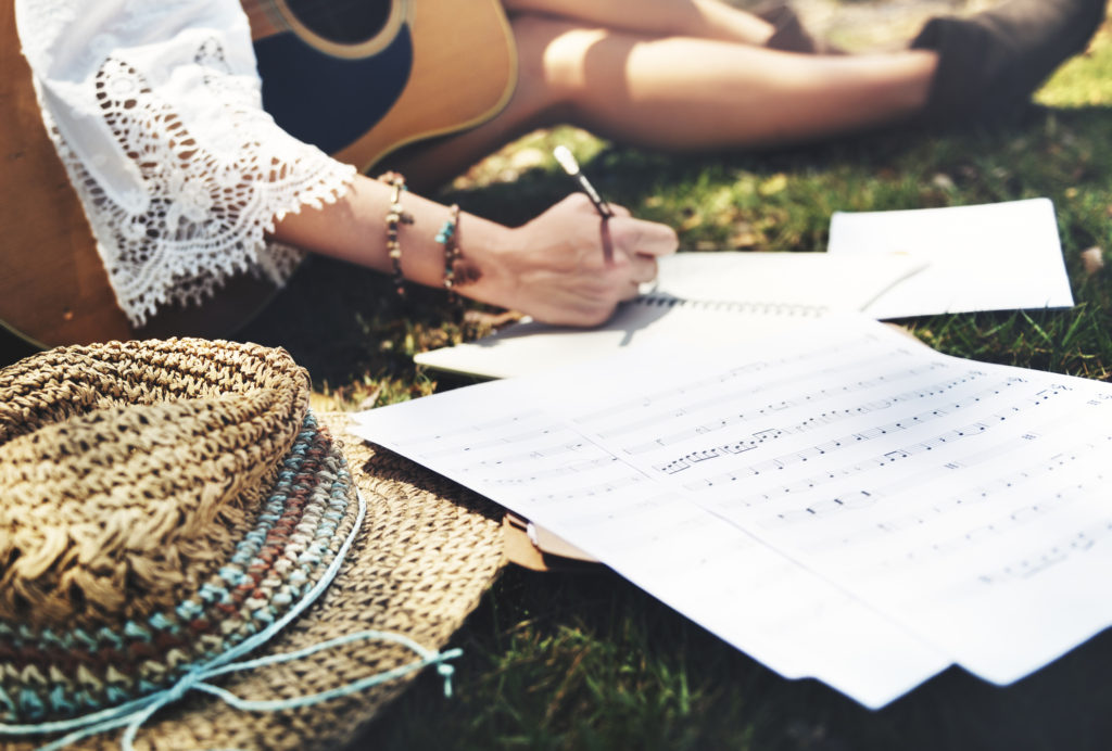 Hippie girl writing songs with acoustic guitar in park.