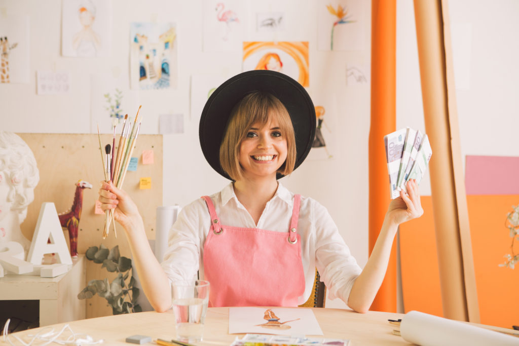 Female artist wearing a hat holding paintbrushes and money.