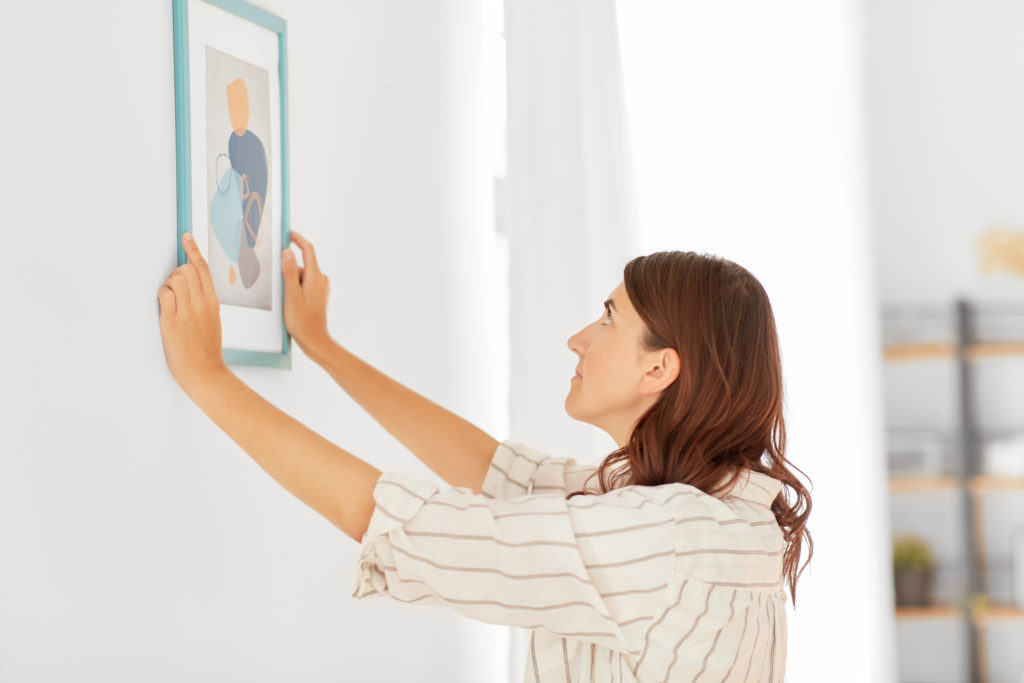 Woman with red hair removing framed artwork from wall.