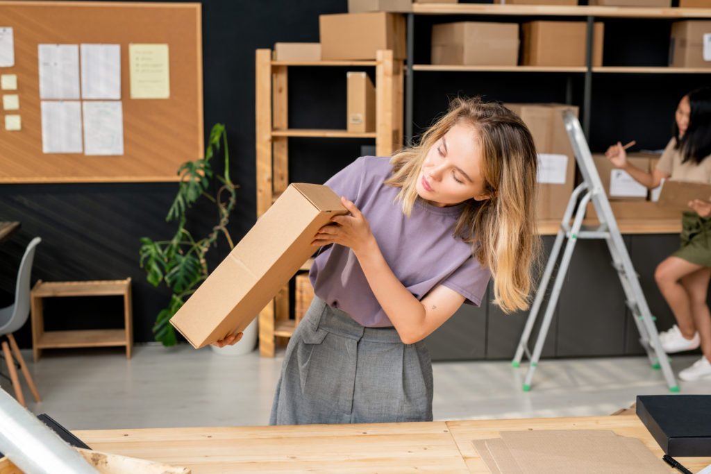 Woman inspecting a box having learned how to ship art