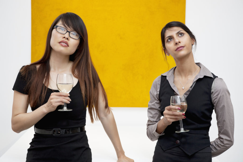 Two women holding wine glasses at a gallery exercising good art etiquette