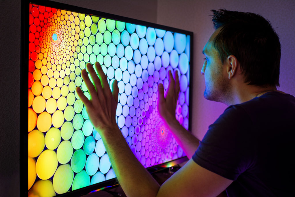 Man looking at TV which is how he likes to display digital art