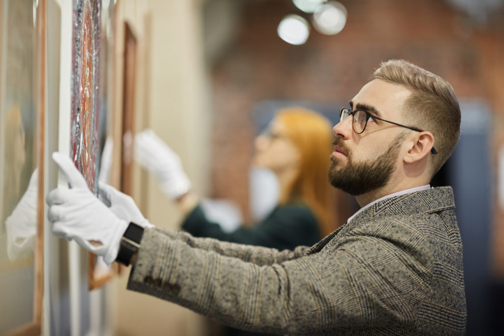 Man with white gloves hanging a canvas who knows how to handle artwork