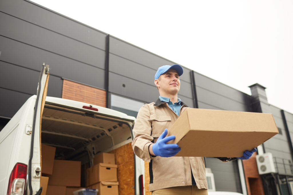 Man behind an courier van delivering a flat box for a customer who doesn't like to travel with art