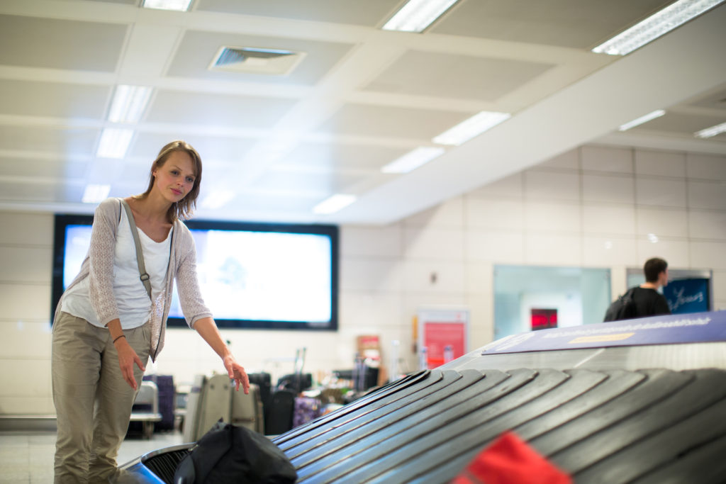 Woman at baggage claim who like to travel with art collecting her bag
