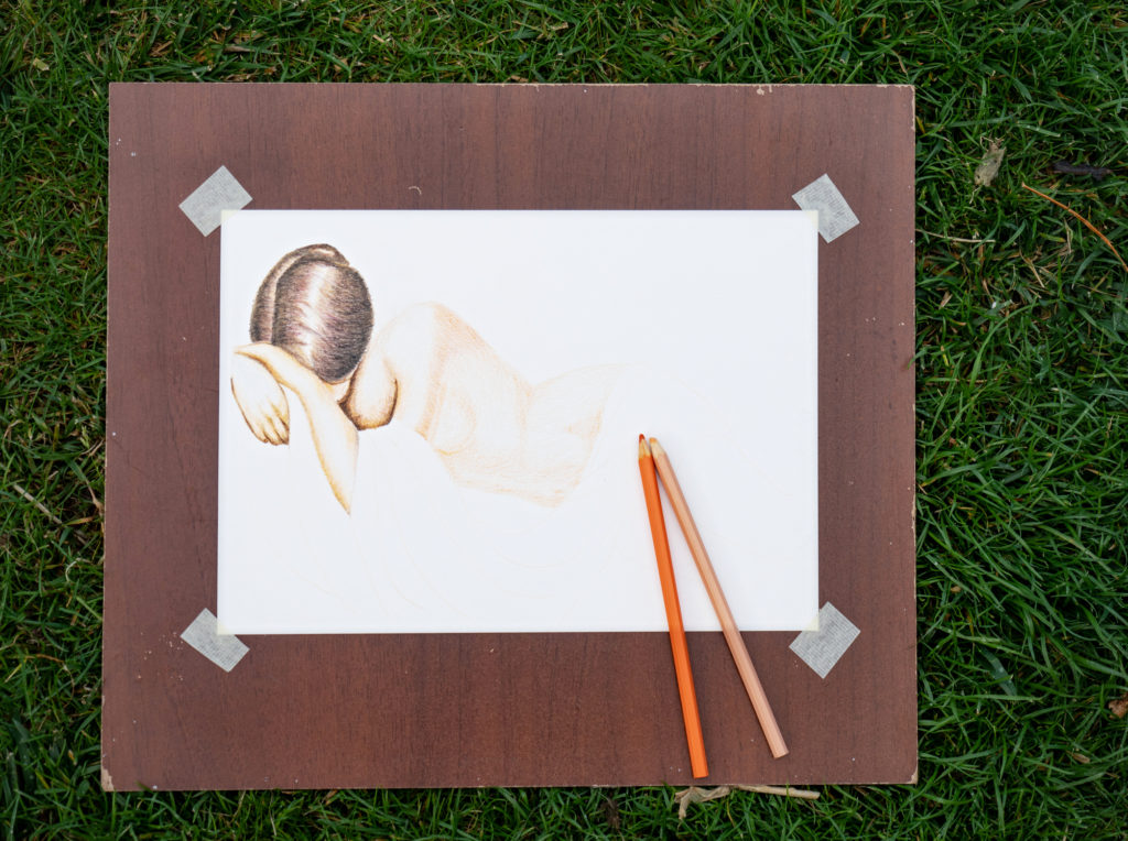 Artist's sketch of a woman on paper that has been carefully affixed at the corners to a board.