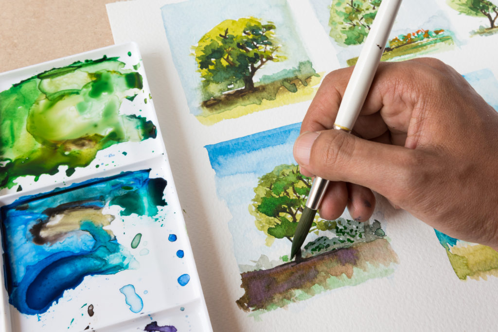 Close up of an artist carefully painting a tree with watercolor.